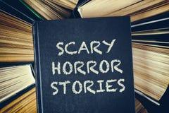 A vista superior de livros de capa dura velhos com histórias assustadores do horror registra o imagem de stock