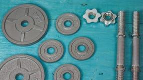 Vista superior de los accesorios para la aptitud en tono gris Pesas de gimnasia, placas del peso Foto de archivo