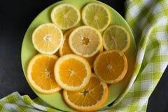 Vista superior de los agrios cortados limón, naranja y descenso en la placa verde sobre fondo negro Fotografía de archivo libre de regalías