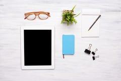 Vista superior de los artículos de la tableta y de la oficina en la tabla de madera Fotos de archivo