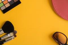 Vista superior de los artículos de los cosméticos en fondo amarillo fotos de archivo