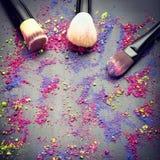 Vista superior de los cepillos del maquillaje en fondo con el polvo del maquillaje Fotos de archivo libres de regalías