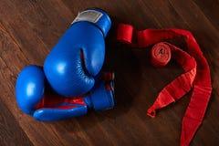 Vista superior de los guantes y del vendaje azules y rojos de boxeo en fondo de madera del tablón Imagenes de archivo