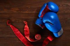 Vista superior de los guantes y del vendaje azules y rojos de boxeo en fondo de madera del tablón Imagen de archivo