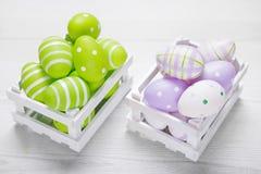 Vista superior de los huevos de Pascua coloridos en la cesta blanca Backgro de Pascua Imagen de archivo