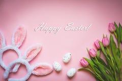 Vista superior de los huevos de Pascua, de los tulipanes rosados y de dos oídos mullidos blancos del conejito sobre fondo rosado  imagen de archivo libre de regalías