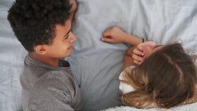 Vista superior de los pares multirraciales felices que mienten en cama y hablar Hombre joven y mujer atractivos en amor Concepto  almacen de video