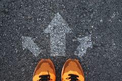 Vista superior de los zapatos del deporte en el camino con las flechas imagen de archivo libre de regalías