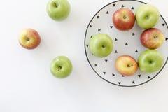 Vista superior de manzanas rojas y verdes en la placa blanca con el modelo negro de los triángulos y de manzanas en el fondo blan Imagen de archivo libre de regalías