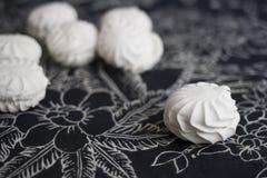 Vista superior de marshmallovs letones - zefiri en el fondo blanco con el mantel floral oscuro Imágenes de archivo libres de regalías