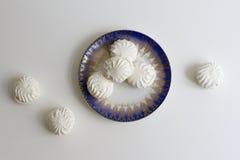 Vista superior de marshmallovs letones - zefiri en fondo del blanco de la placa de la porcelana Imagen de archivo libre de regalías