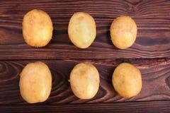 Vista superior de muitas batatas frescas e orgânicas em um fundo de madeira do marrom escuro Batatas novas, close-up Colheita do  Imagens de Stock