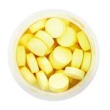 Vista superior de píldoras amarillas en botella plástica redonda Imagen de archivo libre de regalías