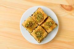 A vista superior de pastelarias mouthwatering do Baklava cobriu com porcas de pistache em uma placa branca servida na luz - tabel fotografia de stock royalty free