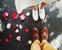 Vista superior de pies de un par joven con poco pétalo color de rosa rojo hermoso en la tierra imagen de archivo libre de regalías