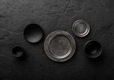 Vista superior de placas e de bacias vazias pretas e cinzentas no fundo de pedra preto fotos de stock royalty free