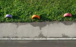 Vista superior de pneus velhos coloridos pintados como um gramado da grama de On The Green da cerca ao longo de Asphalt Sidewalk  foto de stock royalty free