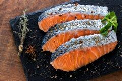 Vista superior de porciones de color salmón frescas en la teja negra fotos de archivo