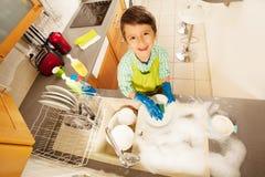 Vista superior de pratos de lavagem do rapaz pequeno no dissipador imagem de stock