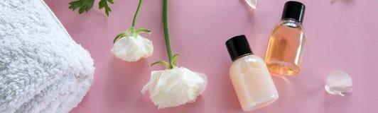 Vista superior de produtos cosm?ticos e de flores delicadas no fundo cor-de-rosa Tratamento da beleza do bem-estar imagem de stock royalty free