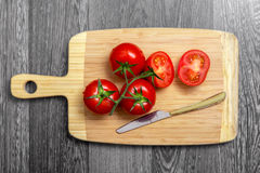 Vista superior de tomates e da faca frescos na placa de desbastamento imagem de stock royalty free