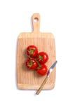 Vista superior de tomates frescos e de uma faca na placa de desbastamento Foto de Stock