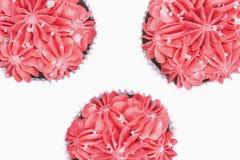 Vista superior de três queques com crosta de gelo cor-de-rosa no fundo branco isolado fotos de stock royalty free