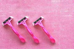 Vista superior de tres maquinillas de afeitar que afeitan rosadas disponibles fotografía de archivo libre de regalías