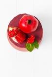 Vista superior de um bolo doce decorado com romã madura em um fundo de madeira branco Fotografia de Stock