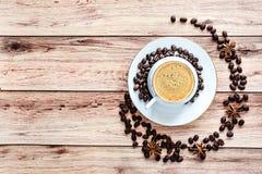 Vista superior de um copo do café quente na tabela rústica de madeira com os feijões e anis derramados de café foto de stock royalty free