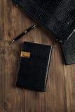 Vista superior de um diário do negócio com uma pena em uma tabela de madeira Imagens de Stock