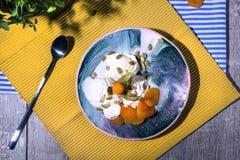 Vista superior de um gelado branco do café da manhã do verão com abricós e uma colher em um fundo brilhante da tela Petiscos frio imagens de stock royalty free