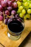 A vista superior de um muscat vermelho e amarelo coloriu a uva e um vidro do vinho em uma placa de madeira - ainda vida Fotos de Stock Royalty Free