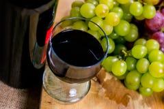 A vista superior de um muscat vermelho e amarelo coloriu a uva e um vidro do vinho em uma placa de madeira - ainda vida Fotografia de Stock