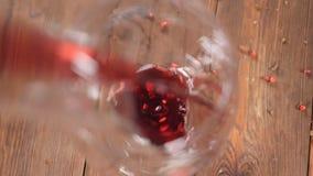 Vista superior de um vidro na placa de madeira marrom O vinho tinto está derramando no movimento lento HD filme