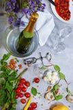 Vista superior de uma tabela cinzenta com placa, champanhe, tomates, aspargo, vidros, corkscrew, feijões em um fundo cinzento Foto de Stock