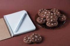 Vista superior de un cuaderno con una pluma en una galleta del chocolate en un fondo rosado Imagen de archivo
