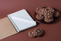 Vista superior de un cuaderno con una pluma en una galleta del chocolate en un fondo rosado Foto de archivo libre de regalías