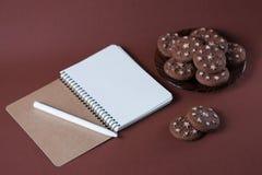 Vista superior de un cuaderno con una pluma en una galleta del chocolate en un fondo rosado Fotografía de archivo