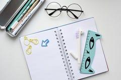 Vista superior de un cuaderno en blanco abierto con una pluma bajo la forma de unicornio, una caja de lápiz con las plumas del ka fotografía de archivo