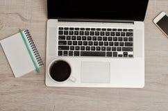 Vista superior de un ordenador portátil, de un teléfono elegante, de un cuaderno con un lápiz y de una taza de café Foto de archivo