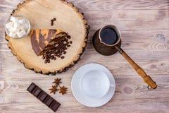 Vista superior de un pedazo de torta de chocolate en tocón de madera con una taza de café, una cuchara del té, una bifurcación, u Fotografía de archivo