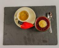 Vista superior de un pequeño café sólo en una taza de la porcelana con la fruta o Imagenes de archivo