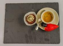 Vista superior de un pequeño café sólo en una taza de la porcelana con las frutas Foto de archivo