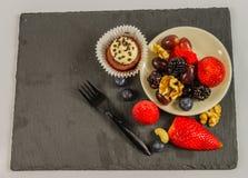 Vista superior de un sistema de diversas nueces y fruta con muffi del chocolate Foto de archivo