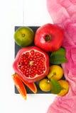 Vista superior de un sistema de las frutas granada, mandarín, anaranjado en el fondo de madera blanco Imagenes de archivo