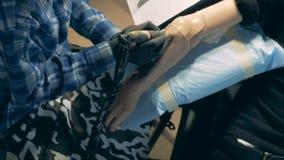 Vista superior de un tatuaje negro-coloreado que consigue dibujado en un brazo sintético metrajes