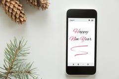 Vista superior de un teléfono móvil, Feliz Año Nuevo en la pantalla Imagen de archivo libre de regalías