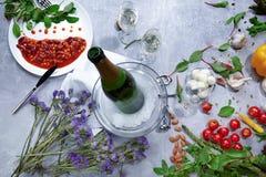 Vista superior de una botella del champán, placa blanca con las habas conservadas, ajo, almendra, tomates en un fondo ligero fotos de archivo