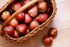 Vista superior de una cesta por completo de manzanas rojas con dos manzanas rojas en el lado Imagen de archivo libre de regalías